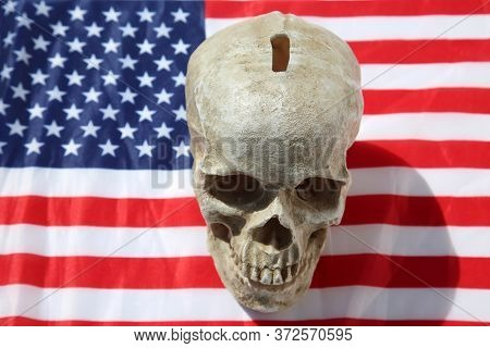 Human Skull Savings Bank on an American Flag. Piggy Bank or Coin Bank made out of a Human Skull on an American Flag.