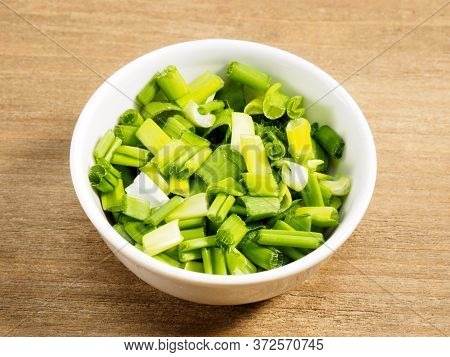 Chopped Green Onion In White Bowl On Brown Wood Background. Healthy Eating, Ayurveda, Naturopathy Co