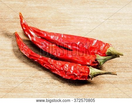 Three Red Chili Pepper Pods On Brown Wood Background. Healthy Eating, Ayurveda, Naturopathy Concept