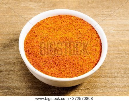 Spice Red Chili Powder In White Bowl On Brown Wood Background. Healthy Eating, Ayurveda, Naturopathy