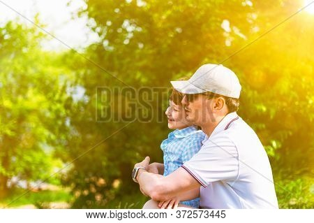Young Caucasian Father And Son Spending Time With Little Son In Park At Sunny Day On Grass. Dad And