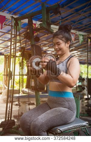 Asian Woman Working Out With Dumbbell Weights At The Gym.fitness Women Exercising Are Lifting Dumbbe