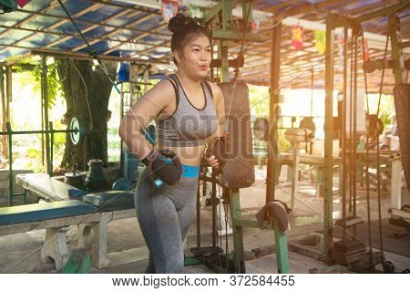 Young Asian Girl Fitness Execute Exercise With Exercise-machine In Gym.