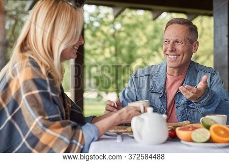 Merry Loving Spouses Enjoying Time Together During Breakfast Outdoors