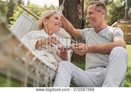 Cheerful Mature Spouses Spending Morning Together In Yard
