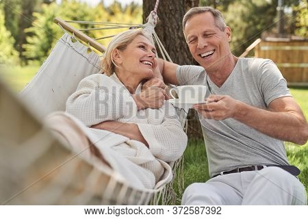 Happy Spouses Having Fun Outside House In Morning