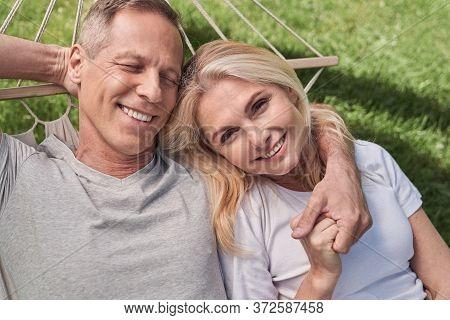 Happy Couple Having Rest In Hammock Outdoors