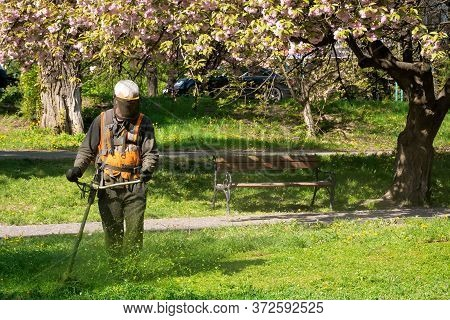 Professional Garden Service At Work. Lawn Care Concept. Cutting An Mowing Grass In The Park. Spring