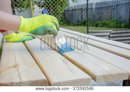 Woman Hand With A Brush Varnishes Old Wooden Boards. Worker Paint With Brush A Wood Wall From Boards