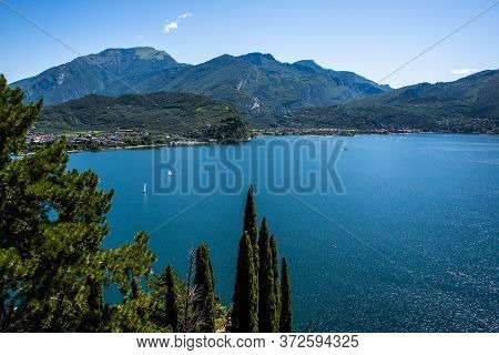 Beautiful View Of Lake Garda From The Ponale Road, With The Blue Sky, Sailing Boats, And The Green O