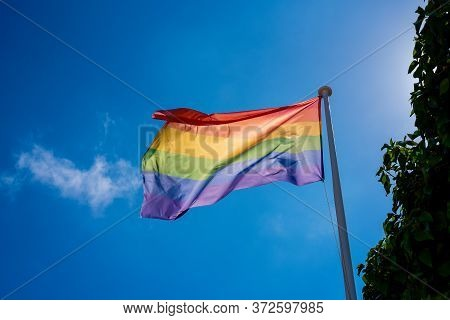 Horizontal Color Image With A Low Angle View Of A Lgbt Pride Flag Hung On A Mast And Waving In The B