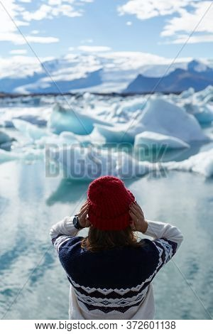 Rear View Of Excited Female Tourist In Warm Clothes Looking At Jokulsarlon Glacier Lake In Iceland,