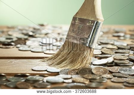 Coins Are Swept Away With A Brush Close-up On A Green Background. The Background In Blurr.