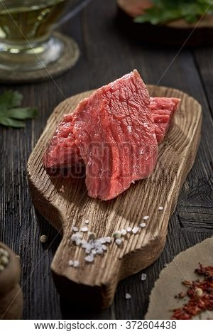 Piece Of Raw Fresh Beef And Coarse Salt On An Old Chopping Board.