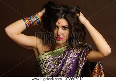Young Woman In The Rich Indian Saris And Colored Bracelets Ruffled Hands Hair. Indian Style.