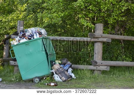Russia, St. Petersburg, June 20, 2020: Large Green Garbage Container Overflowing With Garbage.