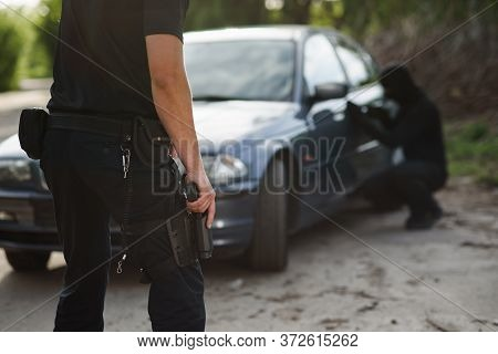 A Policeman With A Hand Gun In His Hand Arrested A Criminal Who Stole A Car. Law And Justice.