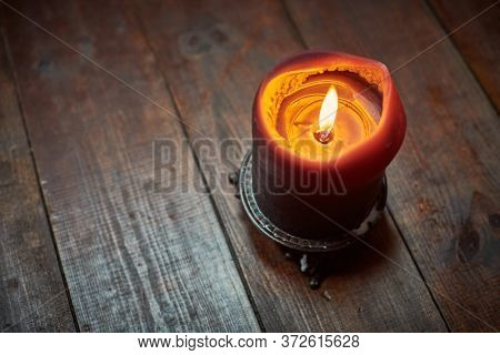 Big Candle On Wooden Table. Burning Candle In A Candlestick, Vintage Gothic Style, Copy Space. Desig