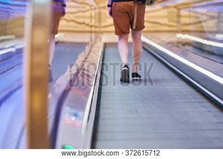Young Man Goes Down On Moving Walkway In Shopping Center. Horizontal Slow-moving Conveyor Mechanism