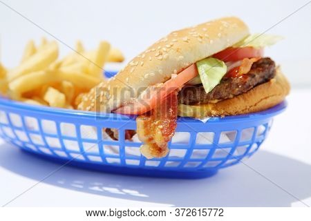Tasty bacon cheese burger with french fries in a blue plastic basket. Room for text. Clipping Path. Bacon Cheese Burger. Lunch. Dinner. American Food. Hot and Fresh Cheese Burger with Bacon and Fries.