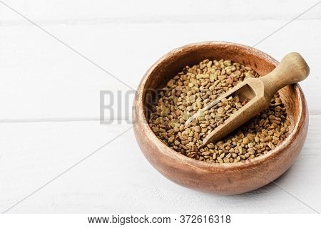 Natural Fenugreek In Wooden Bowl With Spatula On White Surface