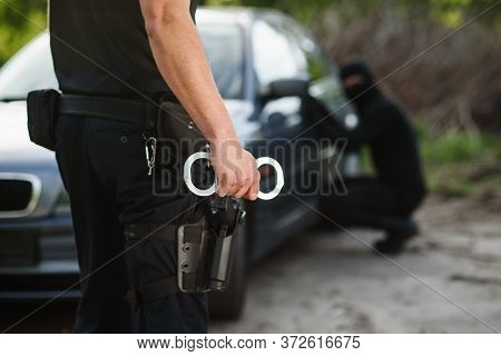 The Police Officer Holding Handcuffs In His Hands. The Policeman Arrested The Offender Who Stole The
