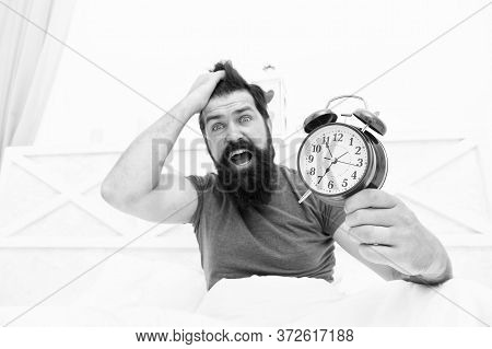 Totally Overslept. Get Up Right Now. Stressed Man Alarm Clock. Sleepy Man Holding Alarm Clock In Bed