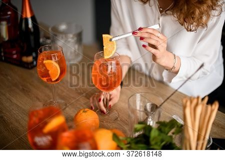 Woman Accurate Decorates Glass With Bright Orange Drink