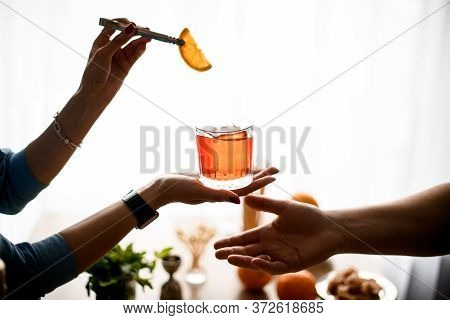 Female Hands Holds Glass With Cocktail And Decorates It And Outstretched Male Hand