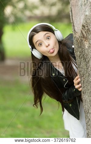 Make Childhood Playful. Playful Girl Stick Tongue At Tree. Little Child Grimace Outdoors. Playful Gr