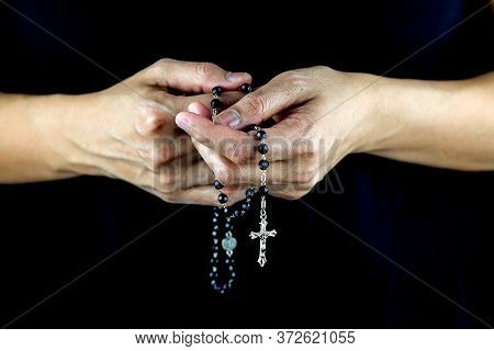 Womans Hands Holding Rosary And Crucifix Against A Dark Shirt
