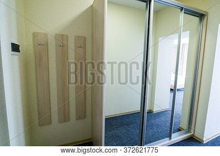 Long Bright Entrance Hall With Doors In A New Hotel With Wardrobe