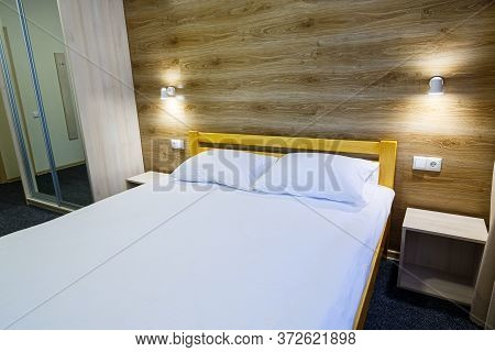 Large Bright Room In The Hotel With A Bed, Tv, Wardrobe. White Bedding. Hotel Room