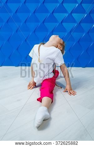 A Little Girl With Pigtails In A White T-shirt On A Blue Background Sits In Twine On The Floor And S