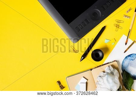 Top View Of Painting, Drawing Tablet With Blank Screen, Clips, Stylus, Notebook And Flower On Yellow