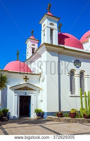 Snow-white church building with pink domes and golden crosses. Israel, Capernaum, Lake Tiberias. Place of worship and pilgrimage. The concept of religious pilgrimage, educational and photo tourism