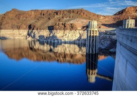 Reflection Of The Hoover Dam And Surrounding Mountains On The Surface Of Lake Mead On The Arizona An