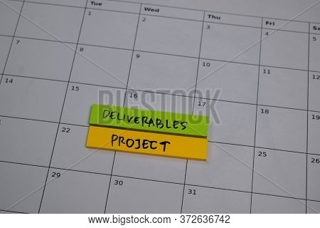 Deliverables Project Write On Sticky Note Isolated On Wooden Table.
