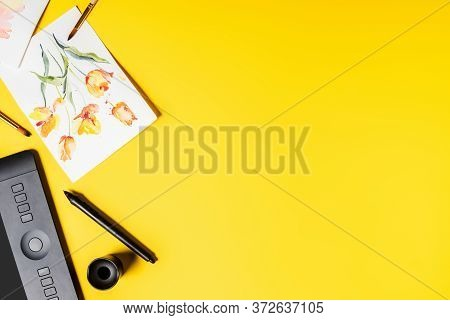 Top View Of Drawing Tablet, Drawn Flowers On Paintings And Paintbrushes Near Stylus On Yellow