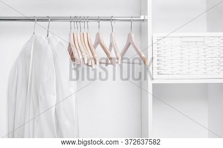 Wooden Hangers And Covers For Clothes In A White Minimalistic Wardrobe.