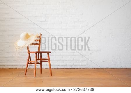 Retro Chair With A Straw Hat On The Background Of An Empty Brick White Wall In The Interior In The L