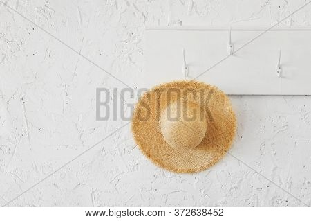 Tropical Wicker Hat On A White Wooden Hanger In A Minimalistic Interior. Travel Delayed During The C