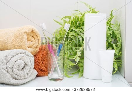 Male And Female Toothbrush In A Glass On A Shelf In The Bathroom. A Towel In A Roll, Hygiene Product