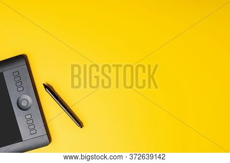 Top View Of Drawing Tablet And Stylus On Yellow