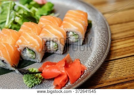 Philadelphia Maki Sushi Made Of Philadelphia Cream Cheese Inside, Fresh Raw Salmon Outside. Garnishe
