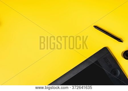 Top View Of Drawing Tablet And Black Stylus On Yellow