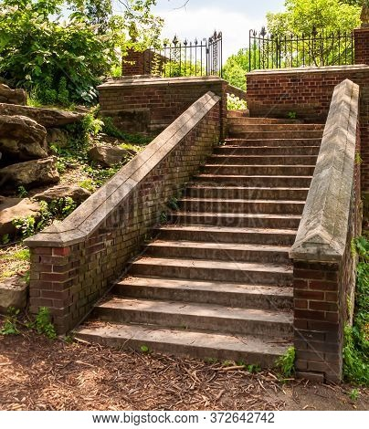 Concrete Steps Lined With A Brick Wall Leading Up To A Landing With A Wrought Iron Fence In Mellon P