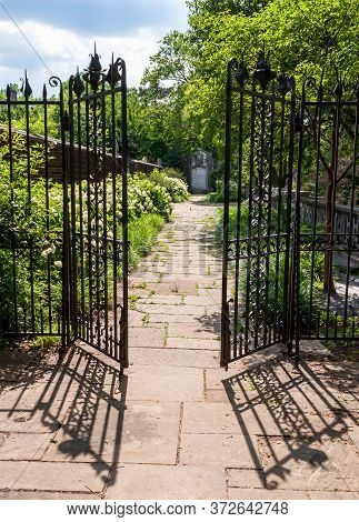 A Stone Walkway Behind An Opened Wrought Iron Fence In A Garden At Mellon Park, Pittsburgh, Pennsylv