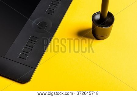 Close Up View Of Stylus In Stand And Graphics Tablet On Yellow Background