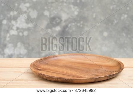 Empty Wooden Tray On Perspective Wooden Table Over Blur Old Gray Cement Wall Background. Can Be Used